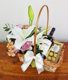 Cesta com arranjo de flores, vinho e chocolate