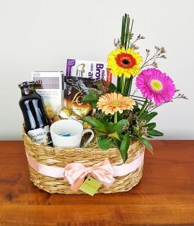 Cesta com arranjo de flores, café e delícias